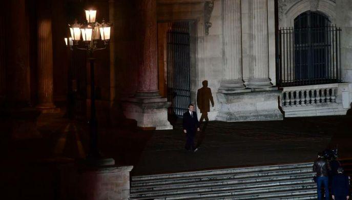 Macron caminando solo hacia el Louvre